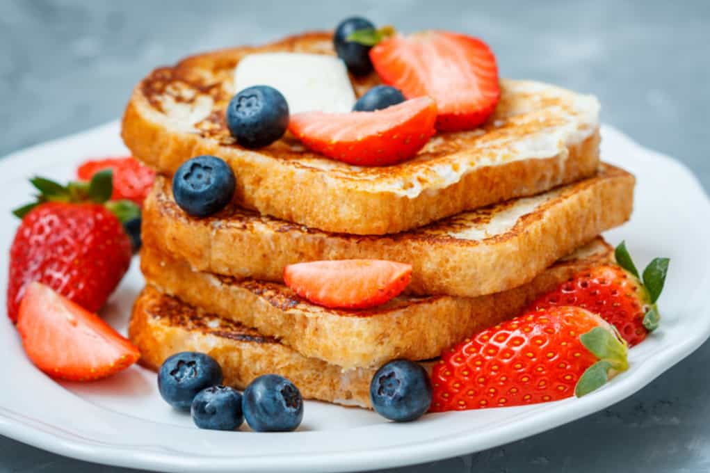 image: four slices of french toast on a plate topped with berries