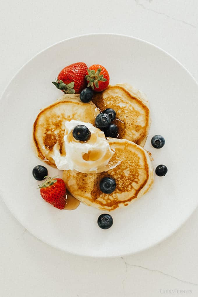 image: overhead shot of three small pancakes on a plate top with berries, syrup and whipped cream