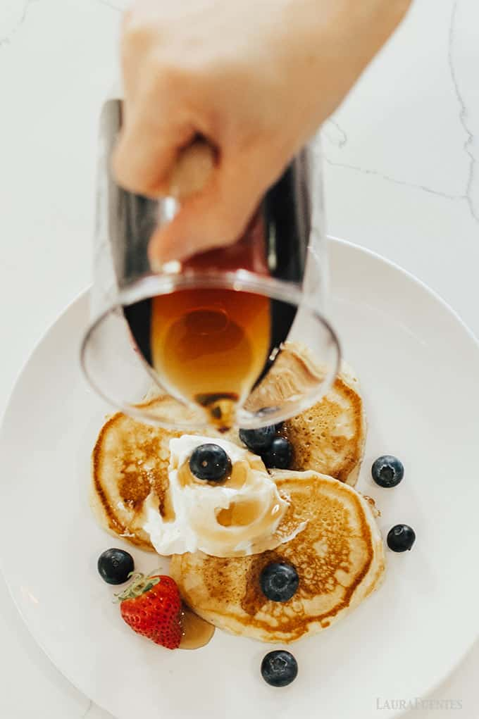 image: three small pancakes on a plate topped with berries. Someone is pouring syrup over the top