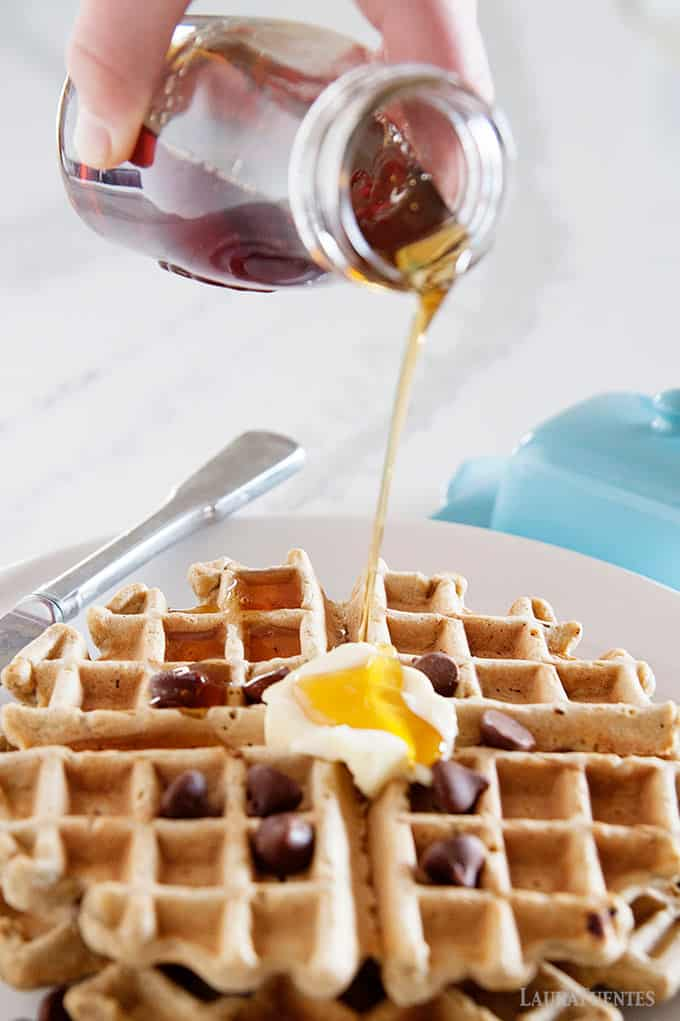 image: pancake syrup being poured over chocolate chip waffles