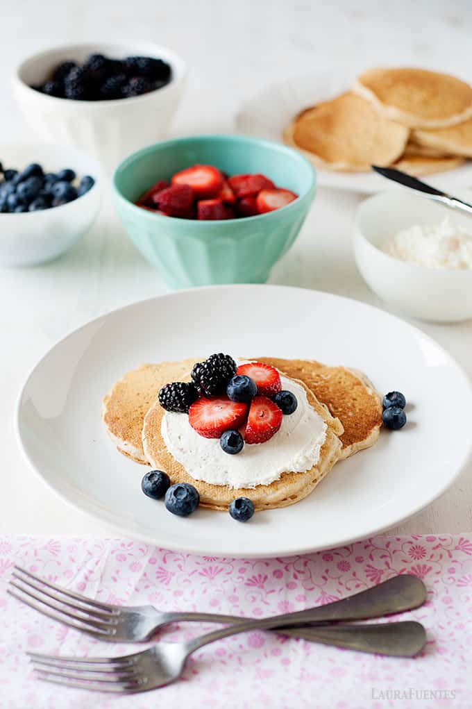 image: three pancakes on a plate topped with cream cheese, and mixed berries. Dishes of pancake toppings are next to the plate of pancakes.