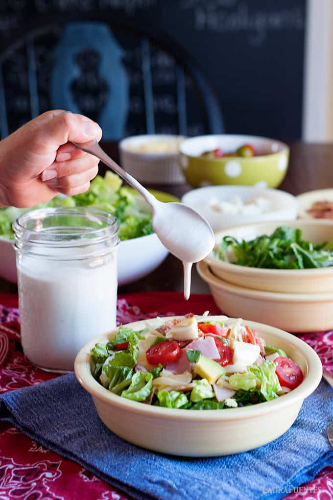 image: jar of homemade ranch dressing, several dishes of salad toppings and one large bowl of salad with. Hand holding a spoon of ranch dressing is drizzling it over the salad.