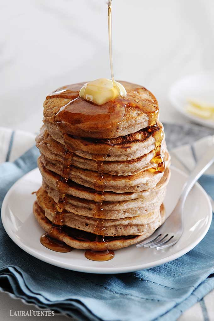 stack of pancakes with butter on top. syrup being poured over stack