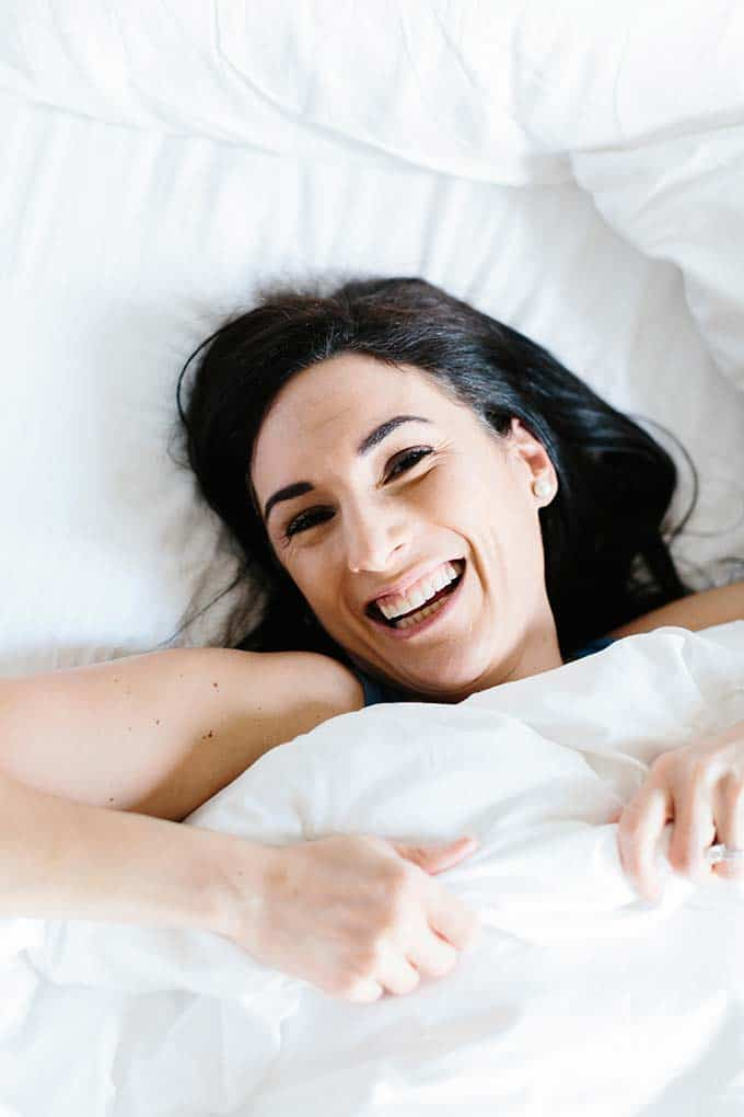 Image: Woman smiling in bed and covered with white blankets.