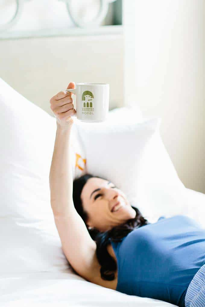 image: smiling woman in pajamas laying in bed holding up a mug of coffee