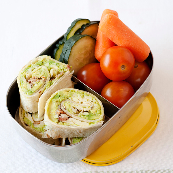 avocado pinwheels in a lunchbox with vegetables