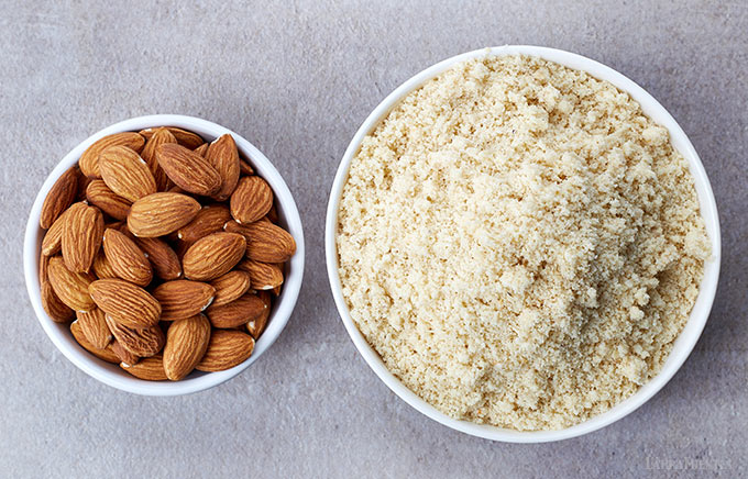 image: two small bowls side-by-side one filled with whole almonds and the other filled with almond flour.