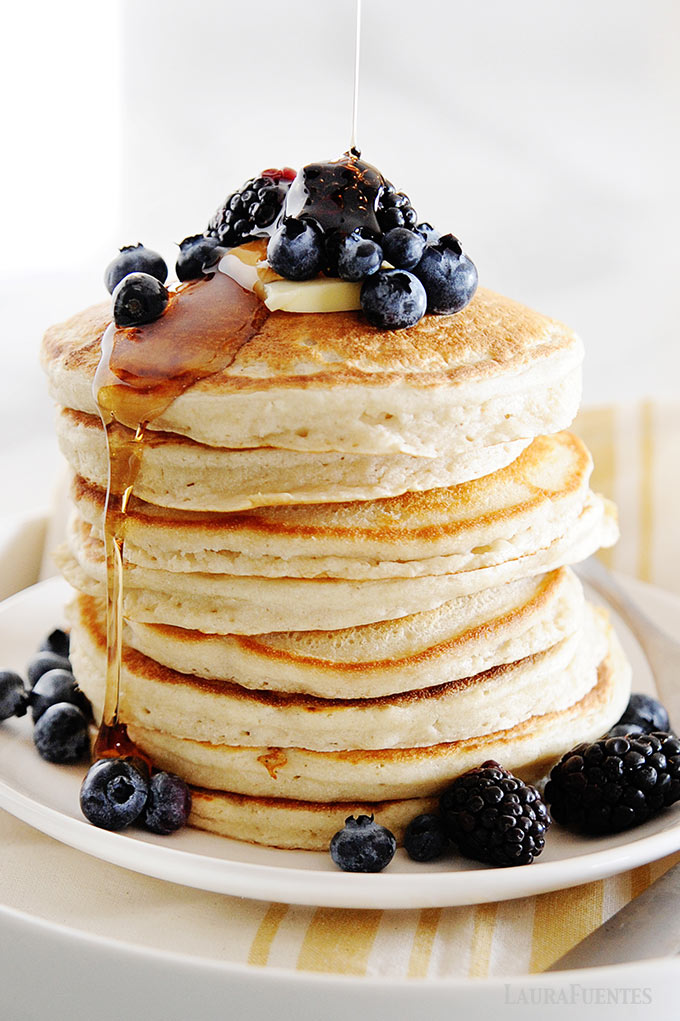 image: stack of cassava flour pancakes topped with berries, butter and syrup.