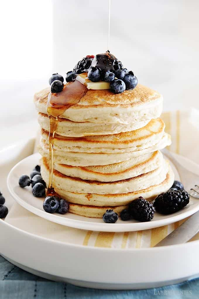 image: large stack of pancakes, topped with blueberries and blackberries, a pat of butter with syrup being poured over the top and drizzling down the sides.