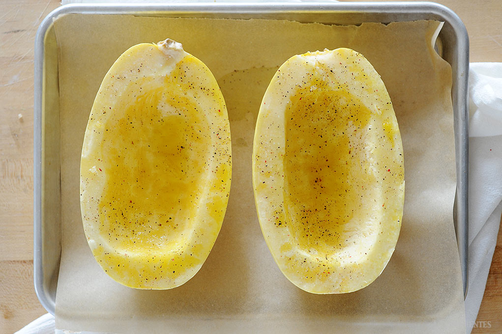 image: two spaghetti squash halves on a baking sheet, lightly peppered