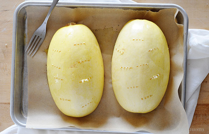 image: two spaghetti squash halves on a baking sheet holes have been poked in the skin of the squash with a fork.