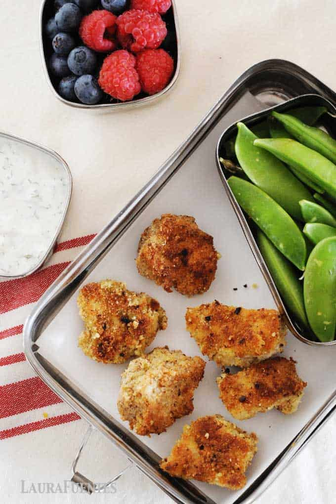 image: Overhead view of six homemade chicken nuggets in a tin lunchbox with snap peas, a small dish of ranch dressing and another small dish of berries.