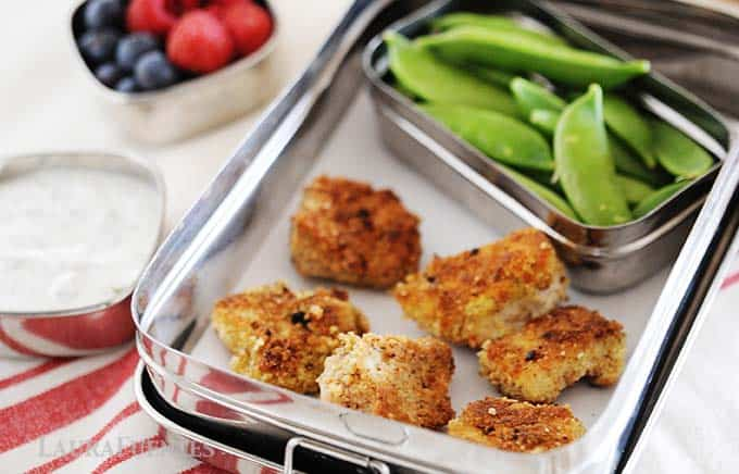 image: six homemade chicken nuggets in a tin lunchbox with snap peas, a small dish of ranch dressing and another small dish of berries.