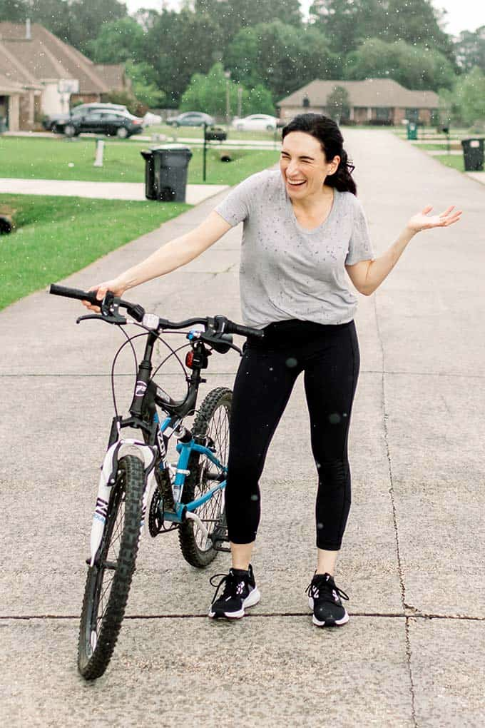 image: Laura standing in the road next to her bike laughing while it rains