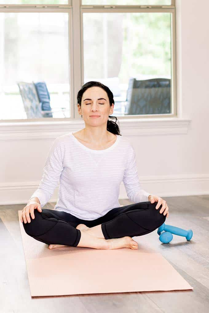 image: Laura seated with eyes closed on a yoga mat in the living room in yoga position.