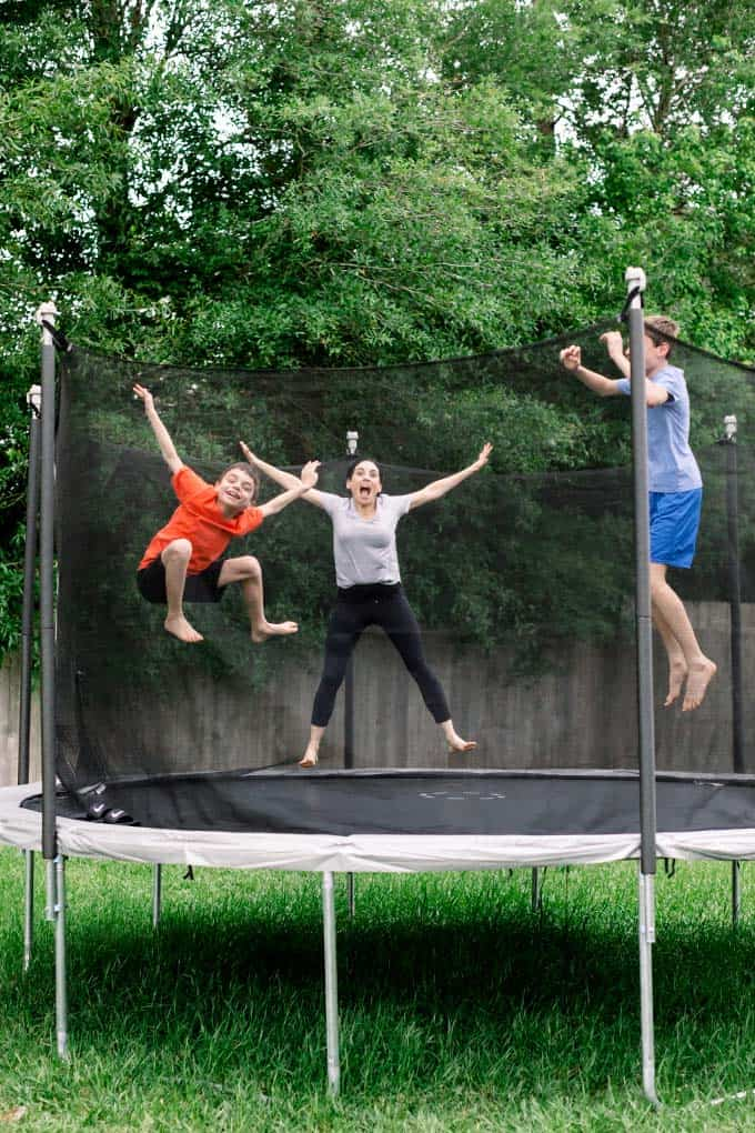 image: mom and two sons jumping on a trampoline together in the backyard.