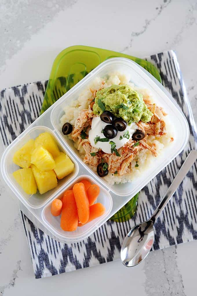 image: overhead view of chicken burrito bowl in a lunchbox with pineapple chunks and carrot sticks.