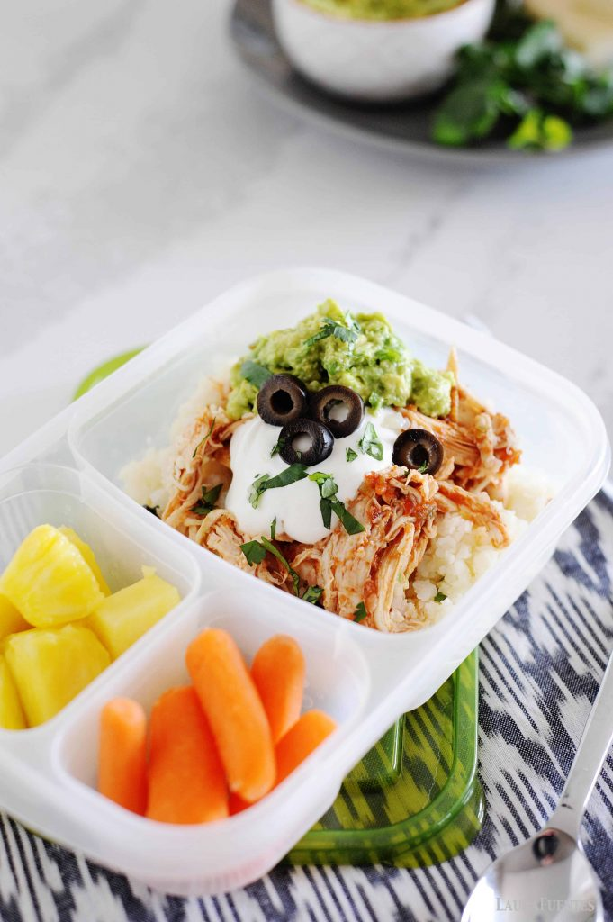 image: low carb chicken burrito bowl in a lunch container. Baby carrots and pineapple chunks are also in the lunch container.