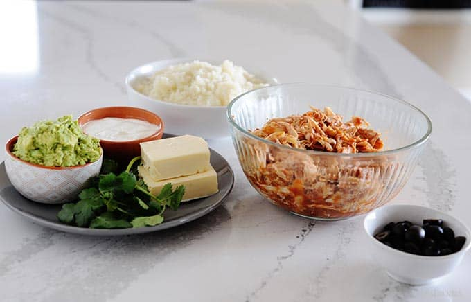image: chicken burrito bowl ingredients laid out in small dishes on the counter.
