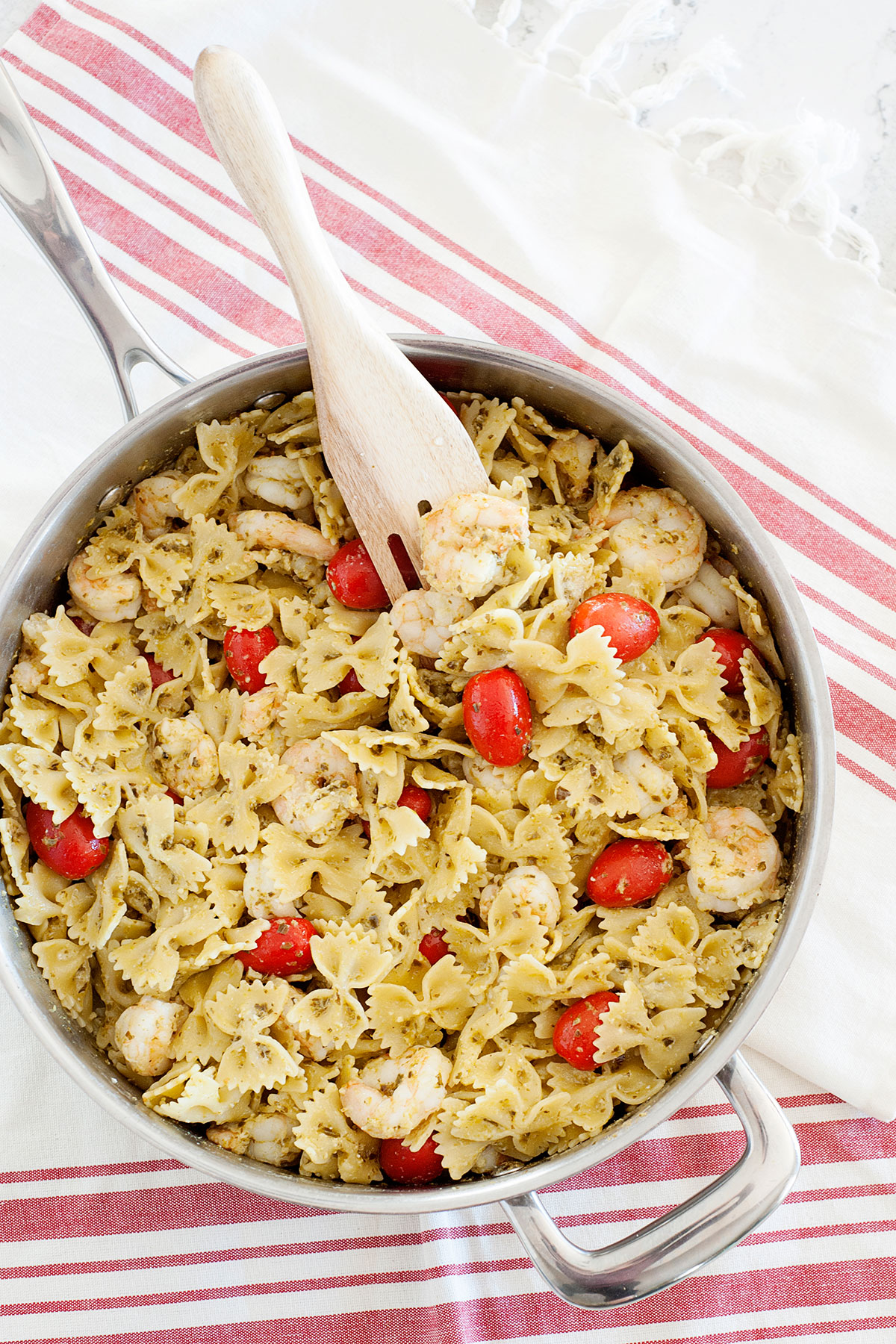 bowtie pasta in a skillet with shrimp and grape tomatoes
