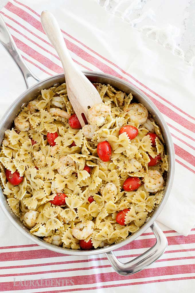 image: bowtie pasta in a skillet with shrimp and grape tomatoes