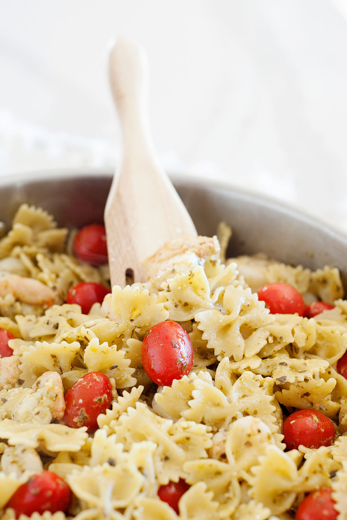 Closeup of skillet with wooden spatula, bowtie pasta, pesto sauce and tomatoes