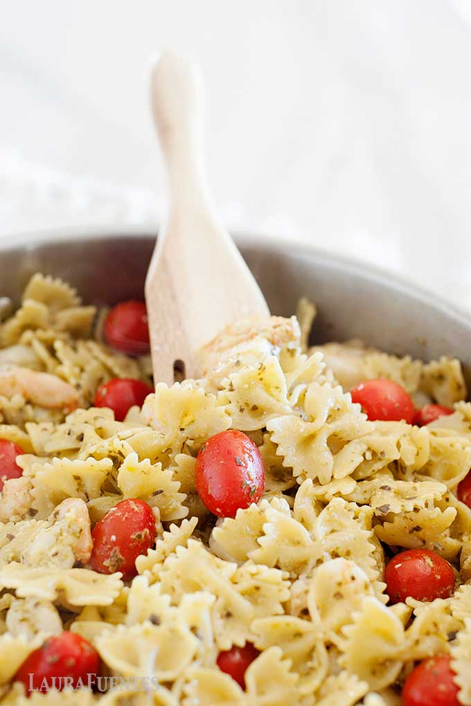 Image: Closeup of skillet with wooden spatula, bowtie pasta, pesto sauce and tomatoes