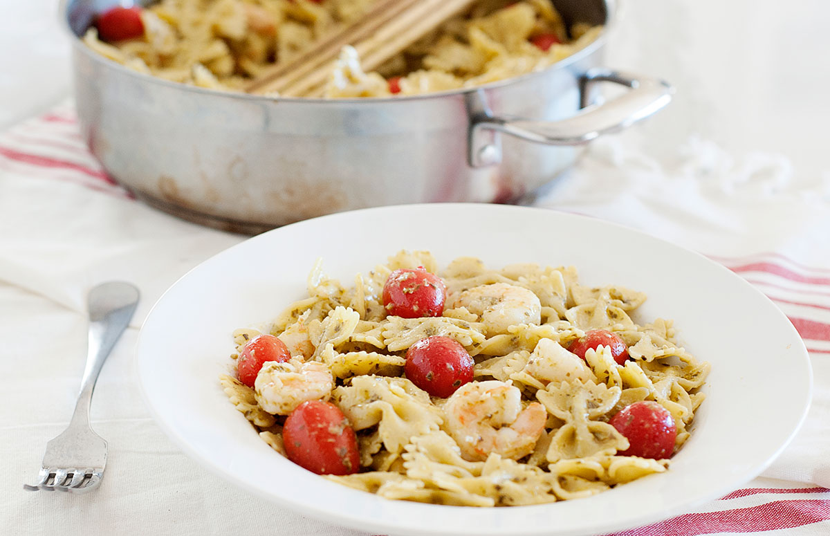 Bowl of shrimp pesto pasta with tomatoes, in front of a skillet full of the pasta