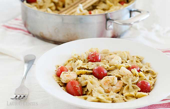 image: Bowl of shrimp pesto pasta with tomatoes, in front of a skillet full of the pasta
