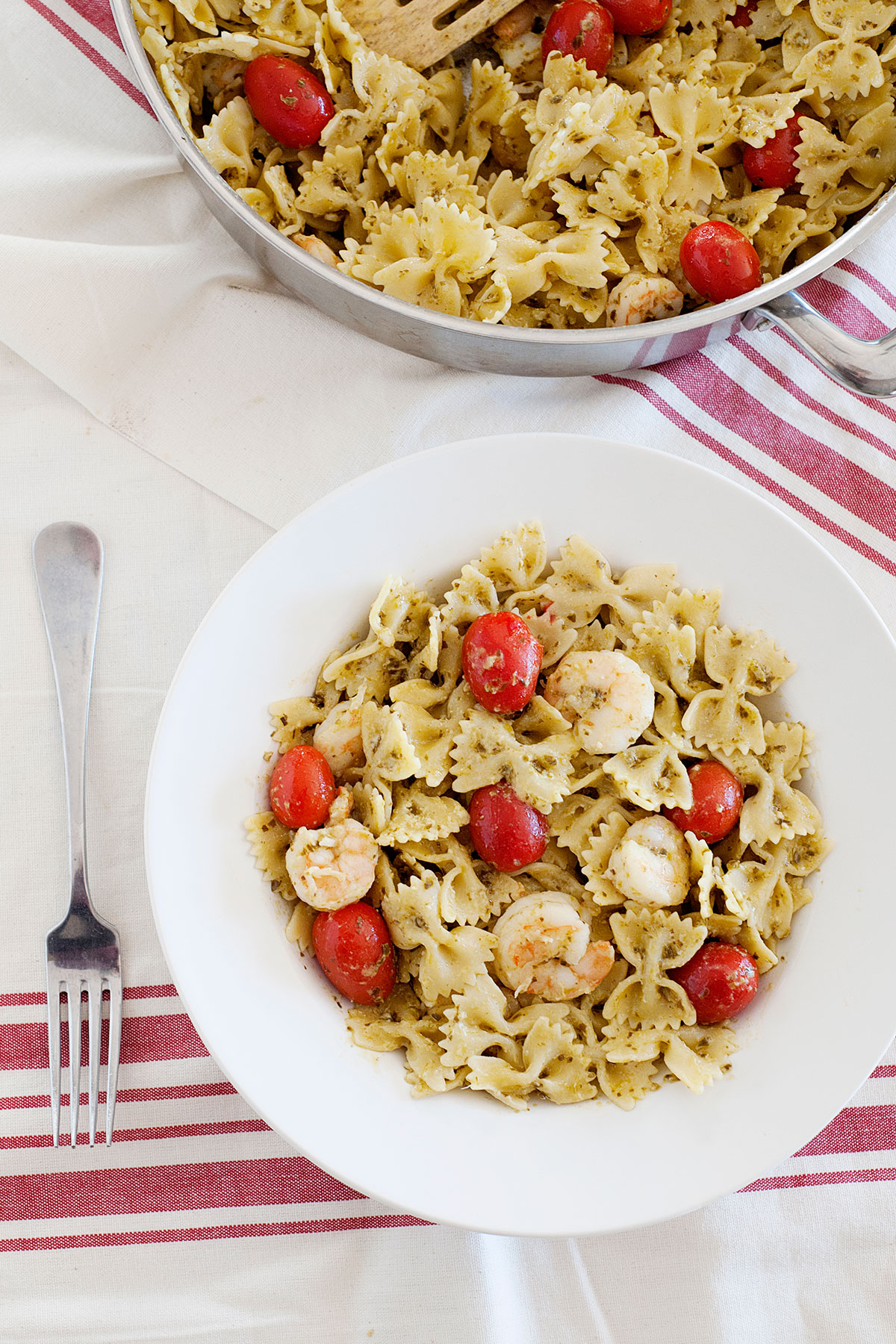 overhead view of shrimp pesto pasta with tomatoes in a bowl, and a skillet full of the same.