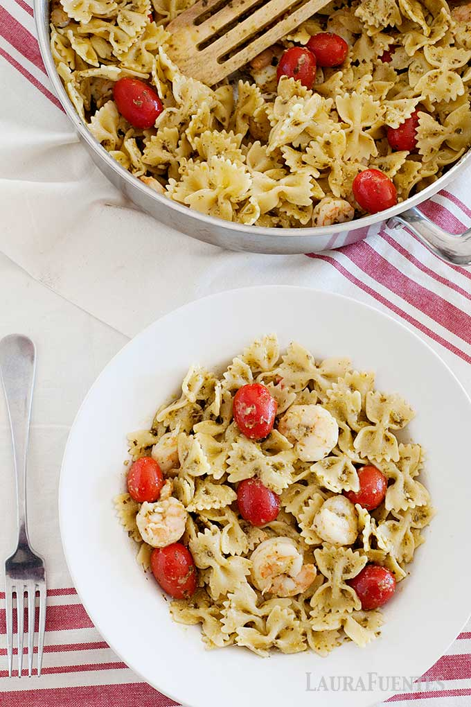 image: overhead view of shrimp pesto pasta with tomatoes in a bowl, and a skillet full of the same.