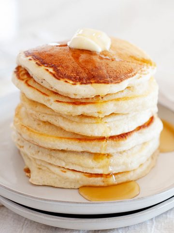 stack of fluffy pancakes topped with butter