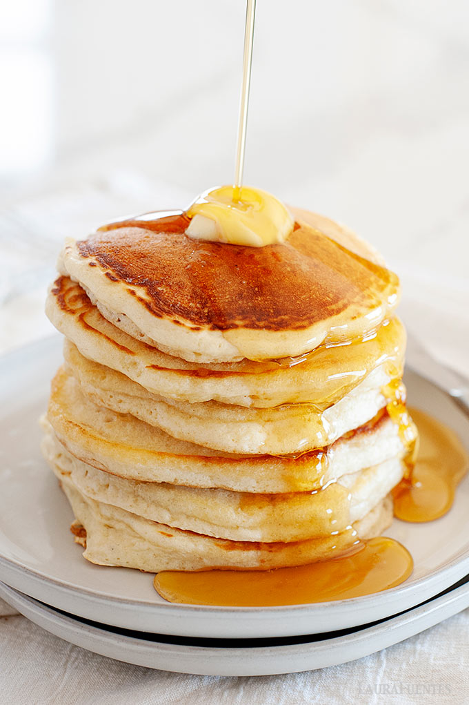 Image: Stack of pancakes on a plate drizzled with maple syrup.