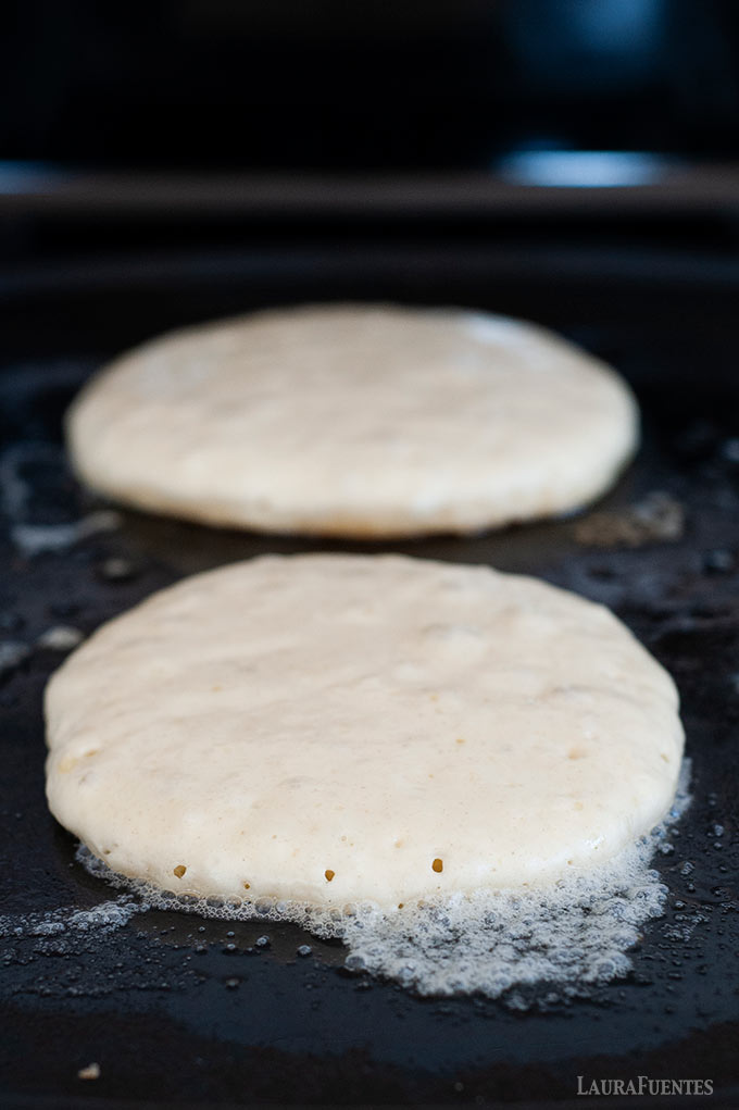 image: two rounds of pancake batter cooking on a griddle, right before it's time to flip them to the other side