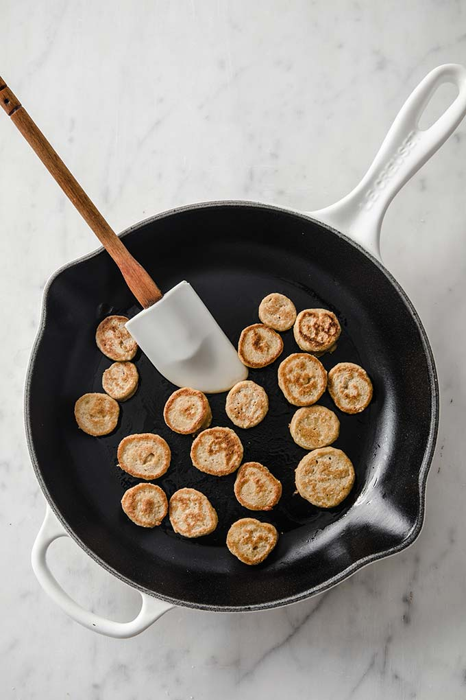 image: mini pancakes flipped and cooked-side-up in a medium skillet with a spatula.