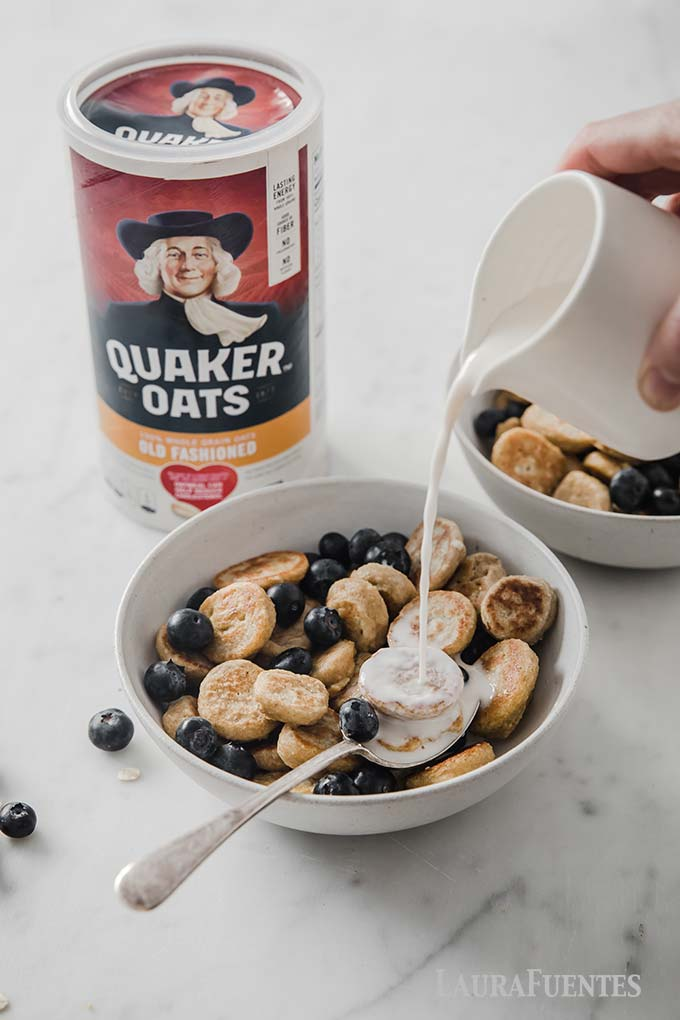 image: pouring milk over bowl of pancake cereal with blueberries. Large container of Quaker Oats behind the bowl.