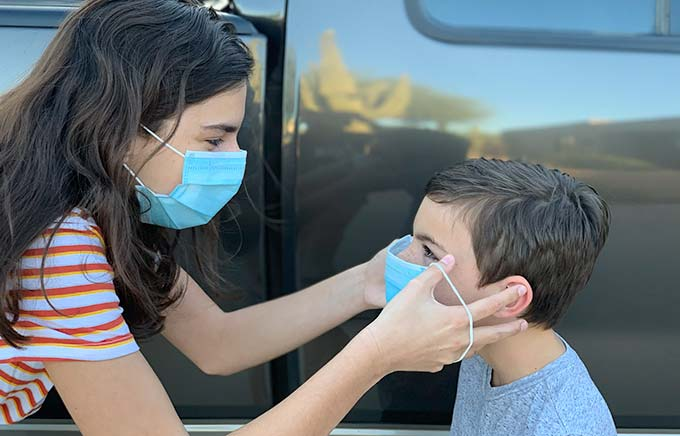 image: big sister putting a mask on little brother outside of the car