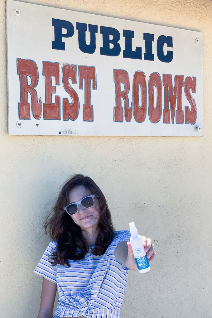 girl holding sanitizer standing in front of public restroom sign
