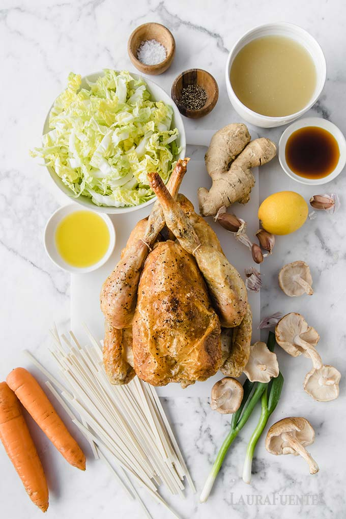 image: roasted chicken, mushrooms, noodles, carrots and other ingredients set out on counter for making udon soup.