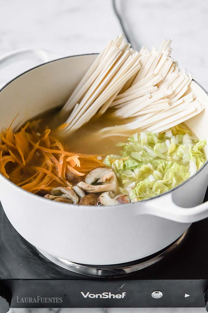 image: vegetables, and noodles in a bone broth cooking in a pot.