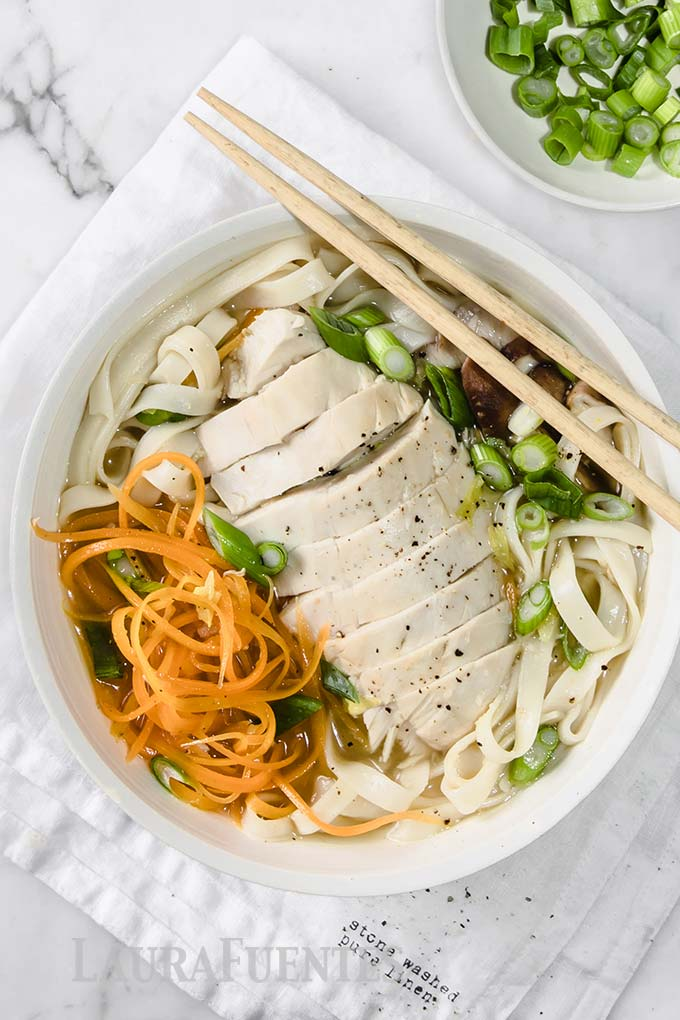 image: overhead view of udon soup with sliced chicken, green peppers and chopsticks.