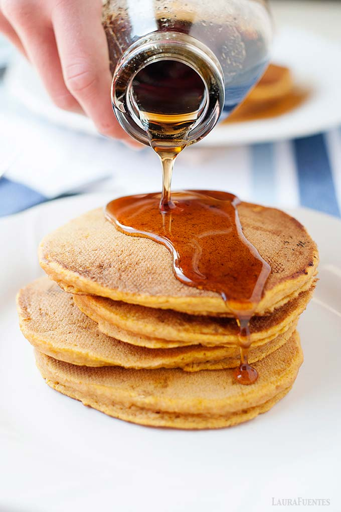 image: stack of pumpkin pancakes on a plate - maple syrup being poured over the top.
