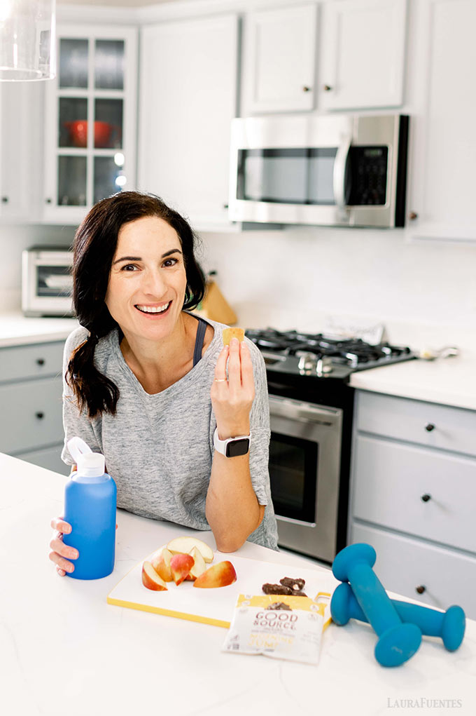 image: Laura in the kitchen with a water bottle and sliced apple