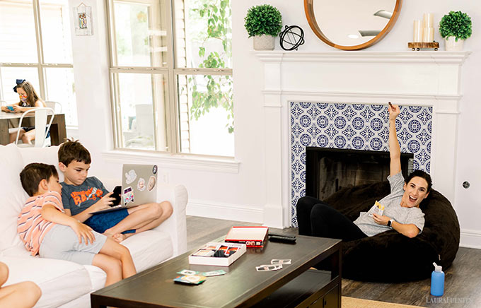 image: Kids playing games in the living room while mom sits on a beanbag chair with healthy snacks and water.