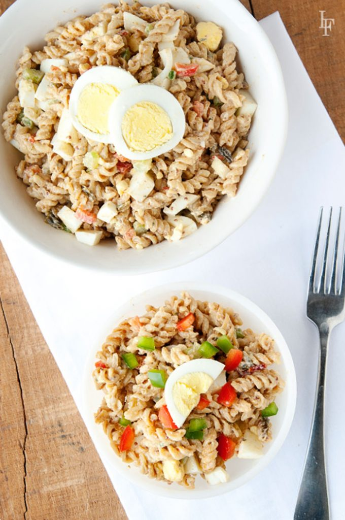 image: one large bowl and one small bowl of Cajun Jambalaya pasta with hard boiled egg slices on top