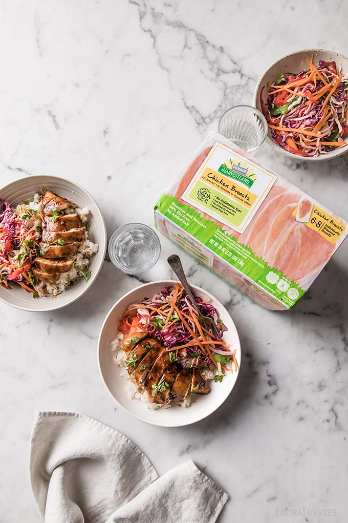 image: three bowls of Korean chicken & slaw with box of Perdue chicken breasts to one side.