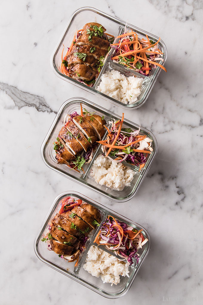 image: three glass lunch containers with sliced chicken breasts, rice and Korean slaw.