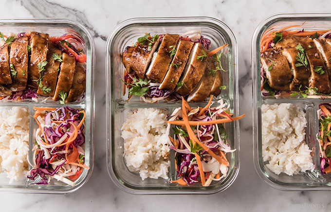 closeup image: three glass lunch containers with sliced chicken breasts, rice and Korean slaw, lined up