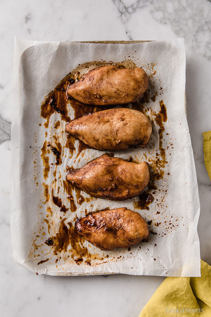 image: four marinated chicken breasts on a lined baking sheet