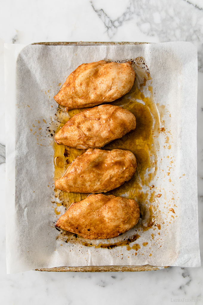 image: four marinated chicken breasts on a baking sheet